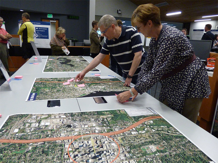 An image shows several people in an office space, with two people examining large aerial maps on a table and placing notes on the maps.