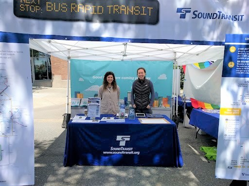 """Two Sound Transit representatives stand in a booth labeled """"Next Stop: Bus Rapid Transit"""" with the Sound Transit logo on the tent. There are project area maps on either side of the booth and informational materials on the booth's table."""