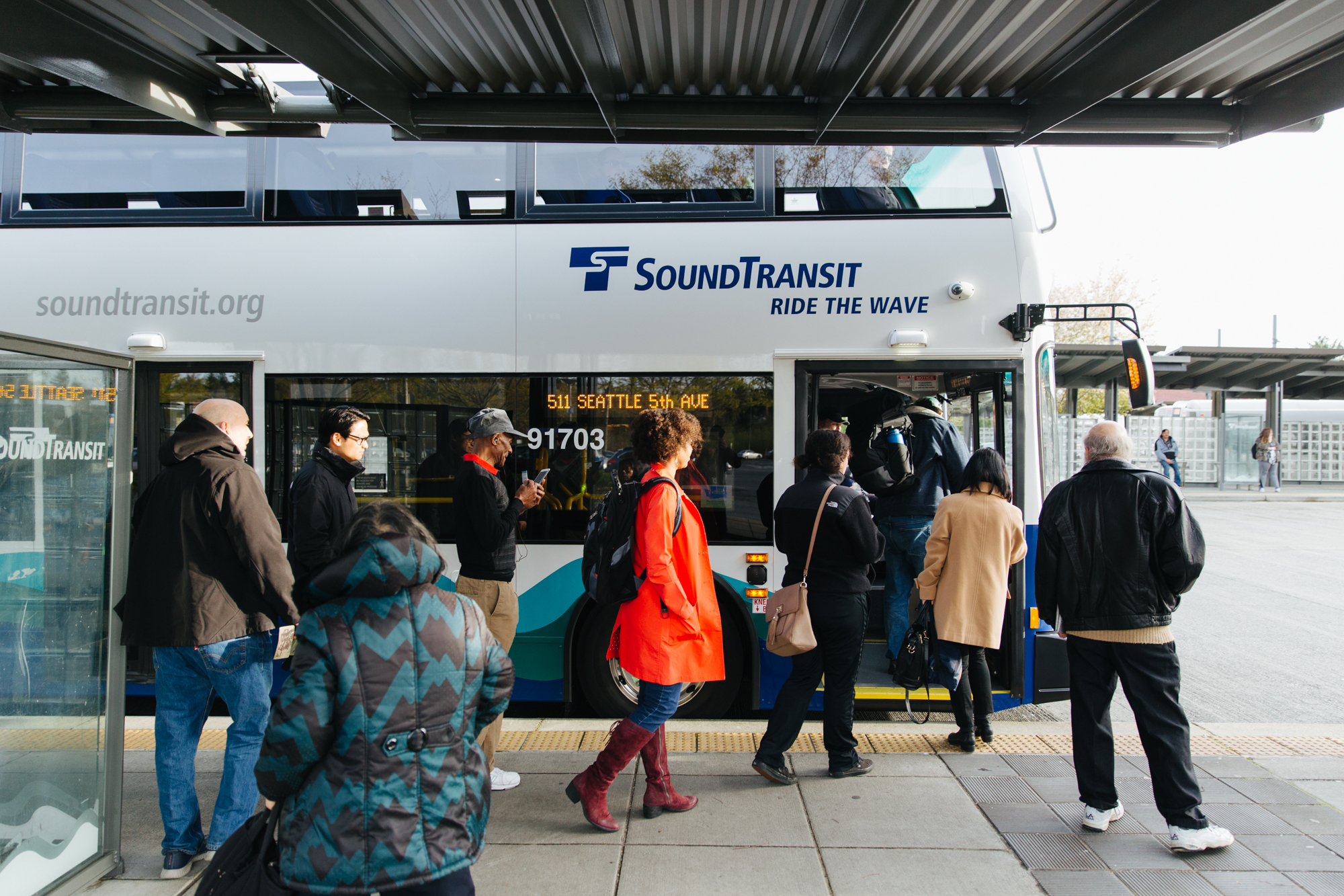 An image shows several people boarding a Sound Transit double-decker bus at a transit station.
